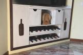 Porta vino, mensola scorrevole poggia bicchieri, due cassetti.