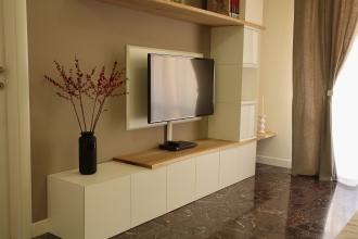 Parete attrezzata: combinazione di cubi laccati bianchi, tavole in rovere, pannello per tv.