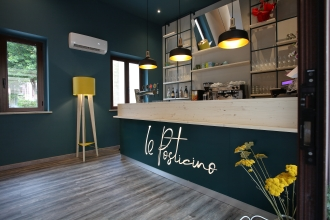 Il Posticino. Progetto e realizzazione di Mastro T + Armoni. | Ingresso. Bancone bar, lampada da terra e parete attrezzata in ferro e legno di abete sbiancato.